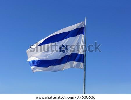 Israel's national flag on blue sky background - stock photo