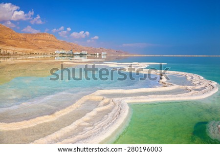 Israeli coast of the Dead Sea. The path from salt picturesquely curls in salty water. Hotels are reflected in smooth water ashore - stock photo