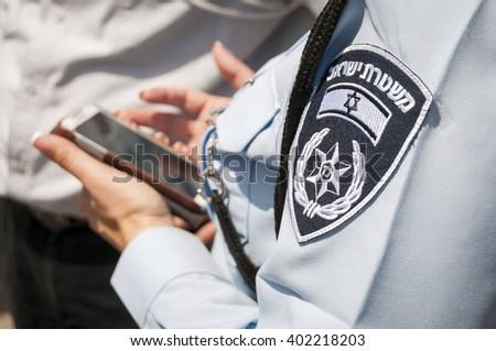 Israeli female police officer with an emblem on her uniform holding cellular phone in her hands. Stock photo image illustration. Tel Aviv, Israel, April 2014. - stock photo