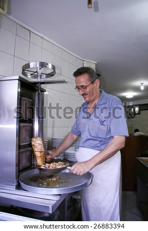 ISTANBUL - AUGUST 5: Little shop owner prepares a kebab for foreign customers in Istanbul, Turkey on August 5, 2007. Istanbul contributes 40% of taxes collected in Turkey. - stock photo