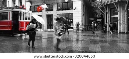 Istanbul in Winter: with motion blur resulting in unidentifiable people walking. Photo in black and white with red pop of moving tram and Turkish flag. - stock photo