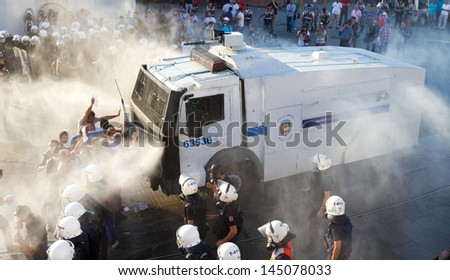 ISTANBUL - JULY 06: Riot Control Vehicle interfere Taksim Solidarity and Gursel Tekin with water spray and tear gas during protests on July 06, 2013 in Istanbul, Turkey. - stock photo