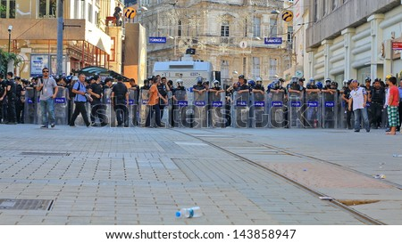 ISTANBUL - JUN 17: Five labor unions call 1-day nationwide strike over crackdown on June 17, 2013 in Istanbul, Turkey. Police lined up against demonstrators during the protest on Istiklal Street. - stock photo
