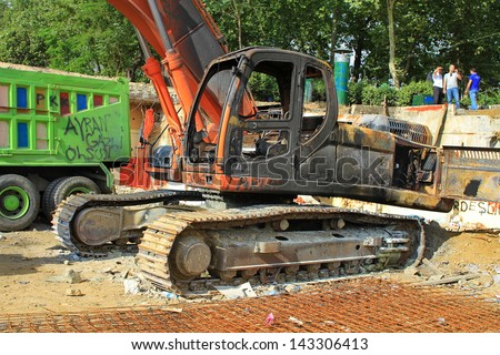 ISTANBUL - JUN 13: Peaceful protest over Gezi Park turns violent as police crack down on June 13, 2013 in Istanbul. Destroyed truck and excavators are seen in worksite after clashes at Taskim square. - stock photo