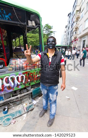 ISTANBUL - JUNE 08: Man with mask in front of damaged bus during protests on June 08, 2013 in Istanbul, Turkey. Guy Fawkes masks widely used and became a symbol of protests in Turkey. - stock photo