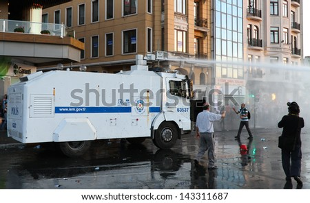 ISTANBUL - JUNE 22: Riot Control Vehicle attack with water cannon on June 22, 2013 in Istanbul, Turkey. People came Taksim Square with carnations to commemoration for dead during protests - stock photo