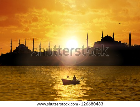 Istanbul silhouette with sun flare and the fishing boat - stock photo