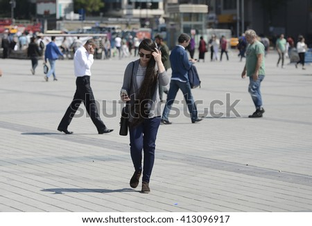ISTANBUL, TURKEY, 28 APRIL 2016, People look at mobile phone while walking on the street.  - stock photo