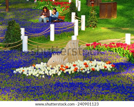 ISTANBUL, TURKEY -- CIRCA APRIL 2014: Sculptures fish among flowering tulips in Gulhane park - stock photo