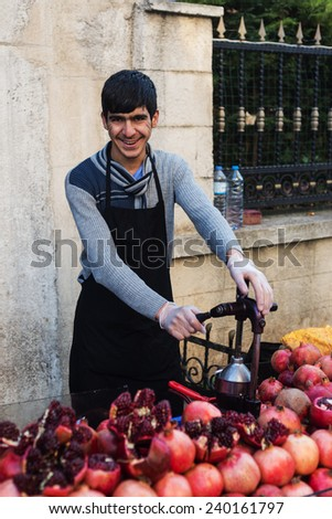 ISTANBUL, TURKEY - DECEMBER 24, 2014:Young man sells pomegranate juice on  Turkey ,December 24,2014. - stock photo