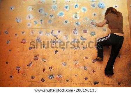 ISTANBUL, TURKEY - JANUARY 29: Rock climber practicing artificial rock climbing on a rock wall indoors on January 29, 2009 in Istanbul, Turkey. - stock photo