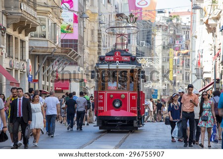 ISTANBUL, TURKEY - JULY 08, 2014 : The Taksim Tunel Nostalgia Tram trundles along the istiklal street and people at istiklal avenue - stock photo