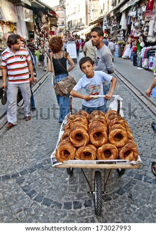 ISTANBUL, TURKEY - JUNE 25, 2010: Grand Bazaar, Unknown Teen sells bagels, June 25, 2010 in Istanbul, Turkey.  Grand Bazaar (founded in 1453) - the largest indoor market in the world. - stock photo