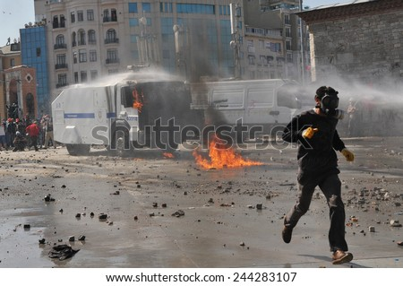 ISTANBUL, TURKEY - JUNE 11: Protesters against the cutting of trees in Gezi Park clash with police. Police use tear gas and water cannon against the protesters June 11, 2013 in Istanbul, Turkey. - stock photo