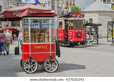 ISTANBUL, TURKEY - JUNE 5, 2016:  The nostalgic tram beside a cart selling traditional Turkish simit at the Taksim end of the famous Istiklal Caddesi.  Tourists and locals enjoy the sunshine. - stock photo