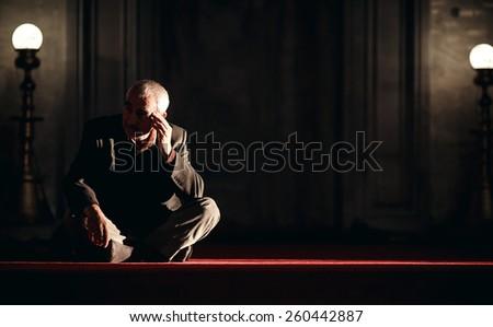ISTANBUL, TURKEY - NOVEMBER 29: Old man sitting on floor in Mosque, Istanbul, Turkey on November 29, 2014 - stock photo