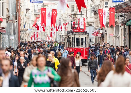 ISTANBUL, TURKEY - OCTOBER 26, 2014: Crowded Istiklal street on a Sunday morning. There are lots of Turkish flags for the Republic Day celebrations that will take place on October 29. - stock photo