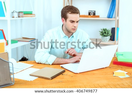 IT company. Young programmer working with laptop. Nice office interier. Professional coder looking at laptop - stock photo