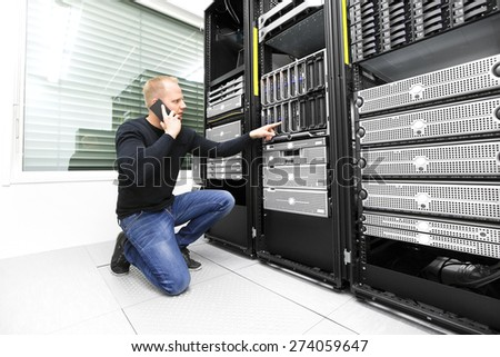 IT consultant calling support in datacenter - stock photo