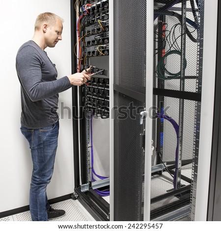 IT consultant install data racks in datacenter - stock photo