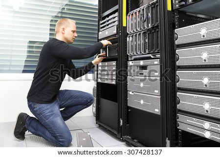 It consultant replaces harddrive in datacenter storage - stock photo