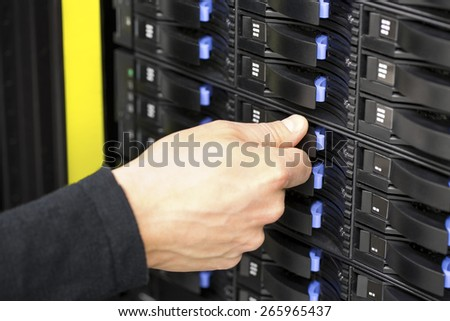 IT consultant replaces SAN harddrive in datacenter - stock photo