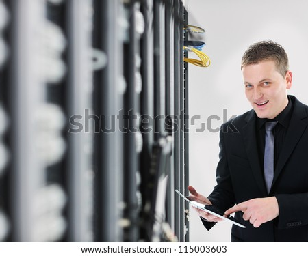 IT engineer business man in network server room using tablet computer - stock photo