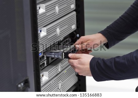 It engineer / consultant working in a data center. Install a new harddisk in a rack server. - stock photo
