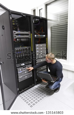 It engineer / consultant working in a data center. Maintain backup. Monitoring with laptop. - stock photo