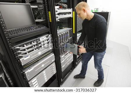 IT engineer installs blade server in datacenter - stock photo