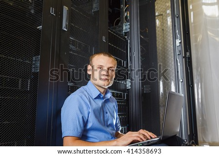 IT Engineer sitting on the floor between the rows in the Data Center and working on laptop - stock photo