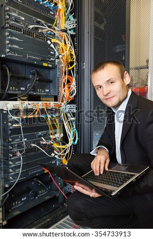 IT Engineer working on a laptop lying in the rack in datacenter - stock photo