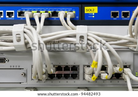 IT environment with switch and firewalls connected with grey patch ethernet cables - stock photo
