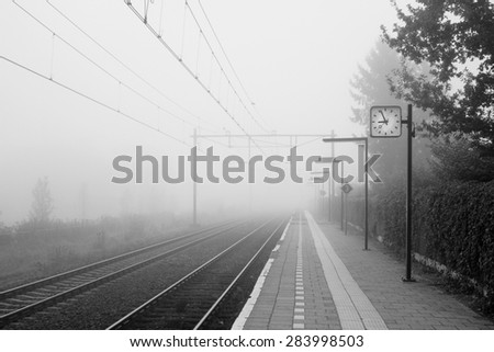It is a foggy October morning at the small Dutch trainstation of Almelo de Riet. It is located near Almelo in the Eastern part of the Netherlands. - stock photo