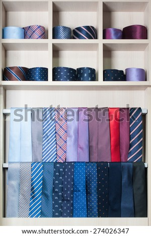 It is a lot of different multicolored ties on a show-window - stock photo