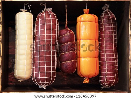 it is a lot of different sausages on a show-window on a black background - stock photo
