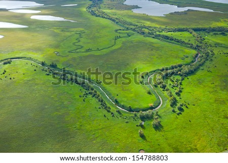 It is aerial view over the small river which is on the green flood-land meadow. - stock photo