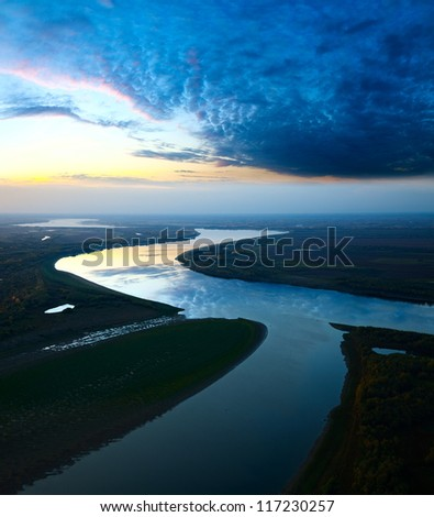 It is aerial view the great river during twilight. On the river is calm now. Beautiful clouds are reflected in quiet water. - stock photo