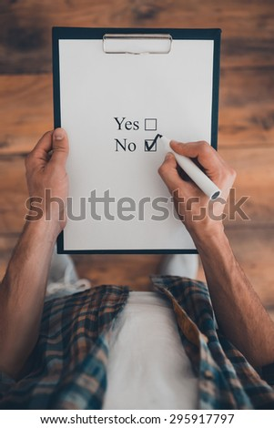 It is no. Top view of man making a check mark in clipboard while standing on the wooden floor  - stock photo