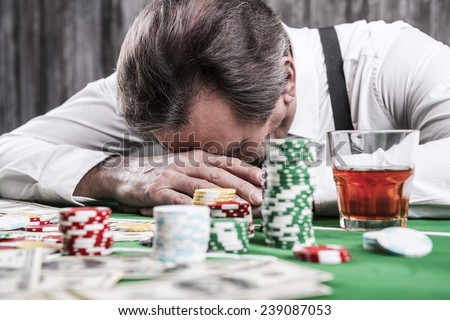 It is not my day. Depressed senior man in shirt and suspenders leaning his head at the poker table with money and gambling chips laying all around him - stock photo