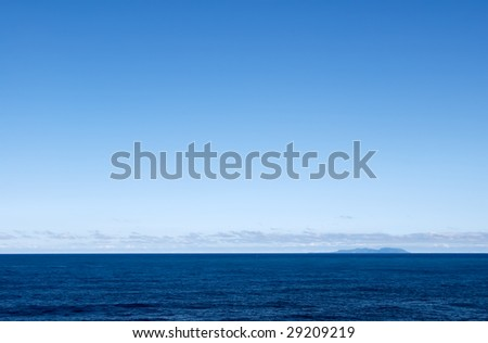 It is the beautiful ocean and small island far away. - stock photo