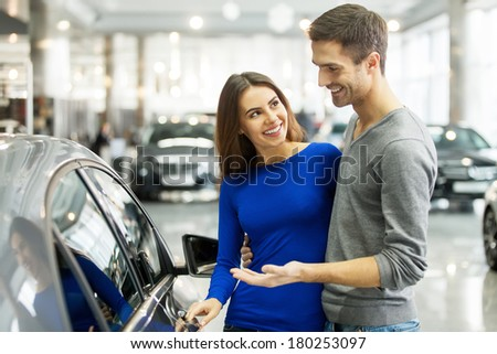 It is the one car I want! Beautiful young couple standing at the dealership choosing the car to buy - stock photo