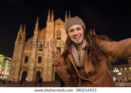 It is time to dress up and take a night tour in ultra-luxurious fashion expert - Milan, Italy. Smiling young woman showing victory gesture and taking selfie in the front of Duomo in the evening. - stock photo