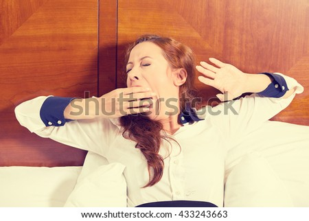 It is too early for meeting. Closeup portrait sleepy young business woman yawning lies in bed trying to wake up for new day eyes closed looking bored. Sleep deprivation lack of adequate sleep concept - stock photo