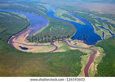 It is top view the confluence of a small river and the old river bed during summer day. - stock photo