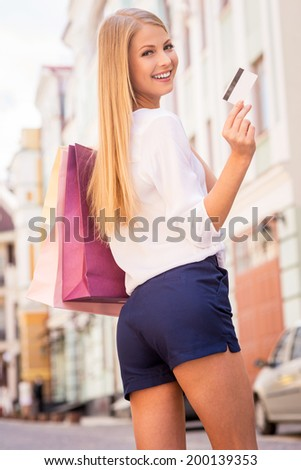It makes my shopping easier. Beautiful young blond hair woman holding shopping bags and looking at camera with smile while standing outdoors - stock photo