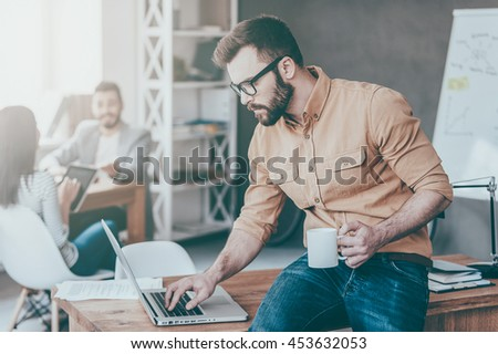 IT professional . Confident young man working on laptop while his colleagues talking in the background - stock photo