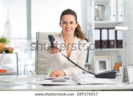 It's for you, says this elegant businesswoman, as she is handing the telephone over with a smile. On her desk, an open ring-binder and agenda. In the background, neat files in a bookcase. - stock photo
