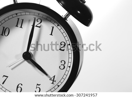 It's four o'clock. An image of a big clock pointing at four o'clock am or pm. Image has a strong black and white effect applied and image is taken in an angle. - stock photo