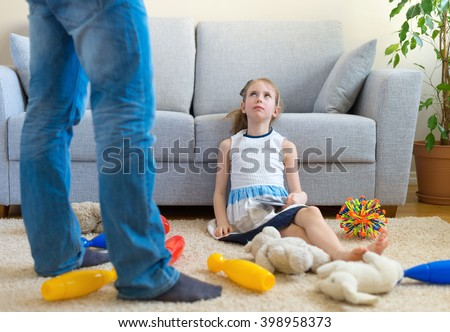 It's time to clean up your toys! Little girl playing with tablet pc, ignoring her father. - stock photo